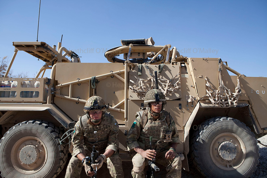 Mcc0027461 . Daily Telegraph..Pvt Lloyd and Pvt Whylie from the FSG (Fire Support Group)B Coy, 3 Para rest up against an armoured reconaisance vehicle prior to a patrol in the Chah e Anjir area , northern Nad e Ali...Helmand 25 November 2010