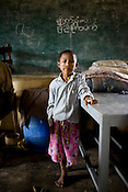 A young boy poses for a portrait in a refugee shelter. Refugees from the Falan village in Kyauktan township take shelter in the Middle school that has been temporarily transformed as a refuge for 18 families and 140 people. .