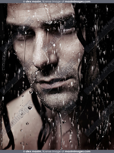 Man face with water running down it and wet long hair, artistic portrait