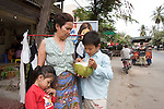 Bunroeun eating a cocunut with his family..A Khmer boy learns to play classical violin at the college of Beaux Arts, at the edge of Cambodia's capital, Phnom Penh. He is an orphan and comes from a poor family. His parents died long ago, from AIDS related diseases. He lives with his grandmother and his uncle, and their family. He lives on the top floor of an apartment block, where his family run a textile business, sewing together clothes and ornamental flags from around the world. A dozen young women work in this textile business, and the boy's home space is actually amidst this small factory environment which he shares with them. They eat, work and play together like an extended family or community. Phnom Penh, Cambodia