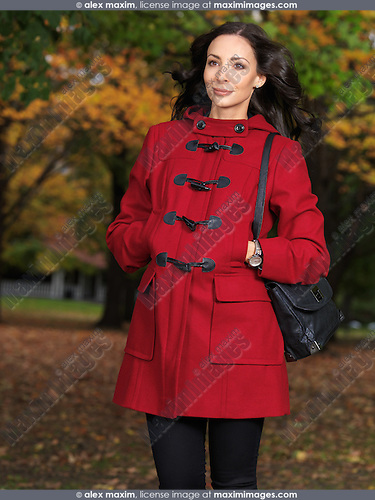 Beautiful young woman walking along the street in fall nature wearing a red coat