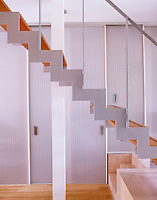 An open-tread staircase with a simple zig-zag steel structure and a wall of storage cupboards with doors of polycarbonate behind