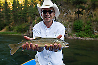 An angler poses with a Bull Trout (Salvelinus confluentus) while fly fishing the Blackfoot River near Missoula Montana.