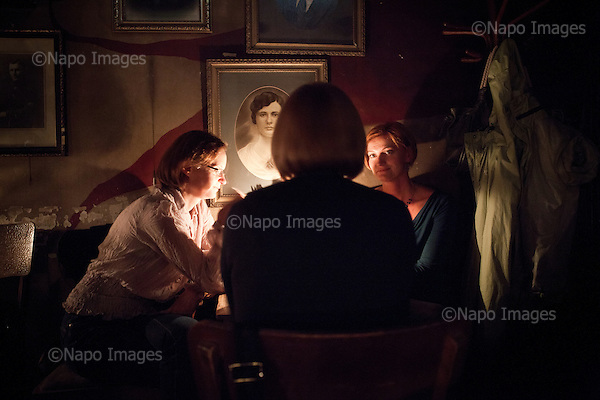 """KRAKOW, POLAND, SEPTEMBER 13, 2011:.Youths are chatting in the evening at the Mleczarnia bar in Kazimierz, former Jewish quarterof the town. Owner has decorated the walls with original vintage portraits that he collected all over Poland..(Photo by Piotr Malecki / Napo Images) ..KRAKOW, 9/2011:.Kawiarnia """"Mleczarnia"""", dzielnica Kazimierz.Fot: Piotr Malecki / Napo Images"""