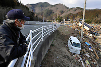 A fisherman looks over a roadside rail at the remains of the hamlet of Toni, near Rikuzen Takata. It was wiped out by the 11 March 2011 Tsunami. His own house was swept four kilometres up the valley. On 11 March 2011 a magnitude 9 earthquake struck 130 km off the coast of Northern Japan causing a massive Tsunami that swept across the coast of Northern Honshu. The earthquake and tsunami caused extensive damage and loss of life.