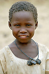 A boy in Labado, one of a handful of people who have returned to the Darfur town that was attacked in December 2004 by government planes and Arab militias, causing the 25,000 residents to flee. The leather pouches around his neck contains verses of the Koran.