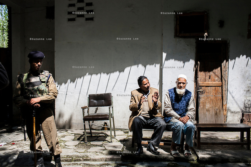 Two elderly kasmiri men chat outside of an empty election booth during the tense election season conflict in Srinagar, Kashmir, India on 7th May 2009. Separatists had warned locals against going out to cast their votes.