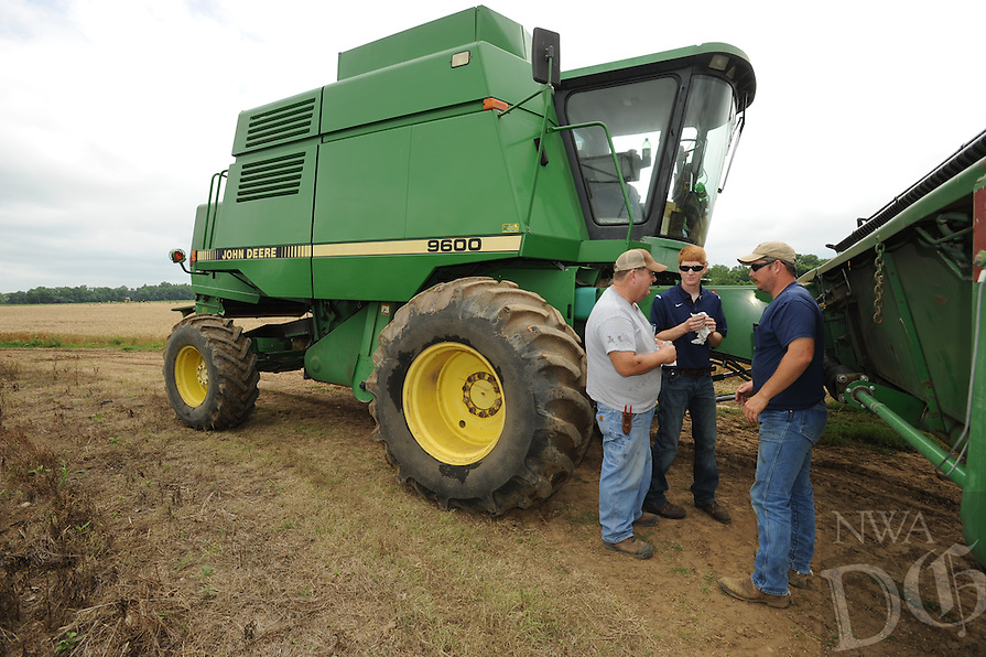 STAFF PHOTO ANDY SHUPE - Allen Moore, right, his brother, Curtis, center, and father, Ralph, reattach the head from their tractor while combining wheat Friday, June 27, 2014, at a farm north of Prairie Grove.