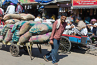 Porters with sacks of dates at Khari Baoli spice and dried foods market, Old Delhi, India