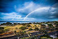 A giant rainbow over O'ahu's Ala Moana Beach Park, with a bird flying through the center of the frame.