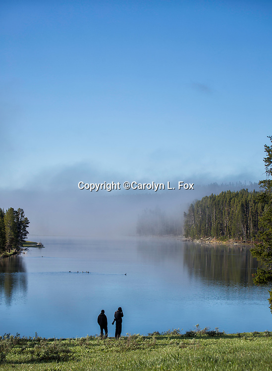 Two men stand next to the Yellowstone River in Yellowstone National Park, on a foggy morning.