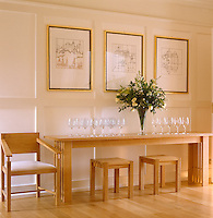 A collection of wine glasses stands on a long, narrow console table above which hang three architectural drawings