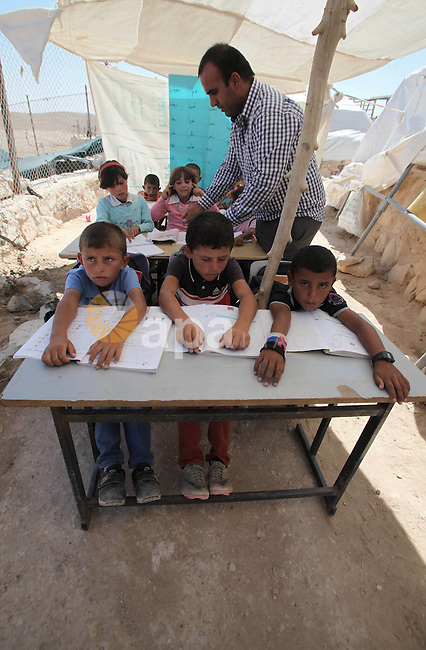 Palestinian children study at a tent in the village of Jimba southern Yatta, near the West Bank City of Hebron, on 01 October 2013. According to reports, Palestinian citizens in the area south of Yatta must leave while Israeli government claims that all eight villages in a so-called 'Firing Zone 918' were merely temporary seasonal residences when the area was declared a closed military zone for training in 1980. The villagers say they have been living there permanently since before Israel's establishment in 1948. Photo by Mamoun Wazwaz