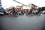 Motorbike riders pass through an intersection at dusk in the Old Quarter of Hanoi, Vietnam. Nov. 12, 2012.