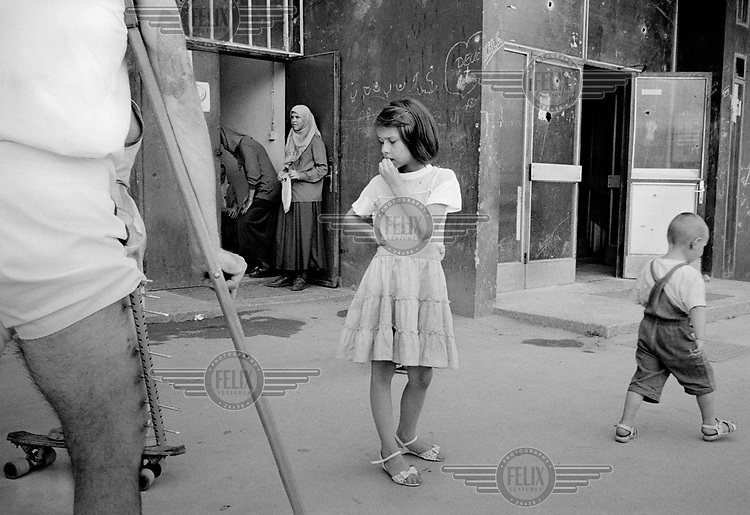 A young girl and her family stand outside their apartment block, in a ceasefire during the siege on Sarajevo by Serb troops. Gas and electricity supplies were cut off for long periods through the 4-year long siege in which over 10,000 people were killed and more than 60,000 were injured.
