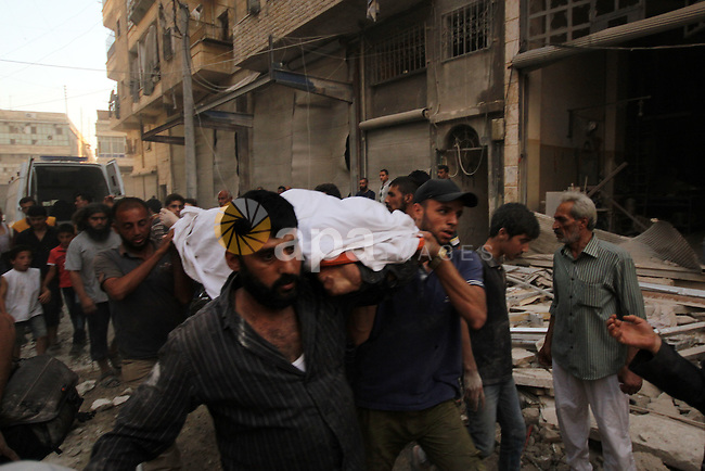 Mourners carry the body of a Syrian man following an air strike by government forces on the al-Mowasalat neighbourhood of the northern Syrian city of Aleppo on September 20, 2015. Photo by Ameer al-Halbi