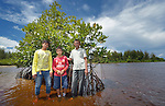 Fajrin and Jefrin Zendrato, and their father Idris, pose among mangroves they planted in 2007 near their village of Moawo on the Indonesian island of Nias. The mangrove planting was part of assistance provided to the village by YEU, a member of the ACT Alliance, following a devastating 2004 tsunami and 2005 earthquake. Residents say the mangroves have helped to protect the shoreline from erosion and attracted crabs and small fish which have helped to revitalize their fishing industry.