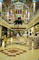 Dubai, United Arab Emirates.  Bur Juman Shopping center/centre/mall. Modern shopping centre/center with traditionally dressed Arab men and people of other races in western dress..
