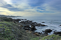 Cloudy and misty with calm seas, the rocky coast at Bean Hollow State Beach as morning light pokes through.
