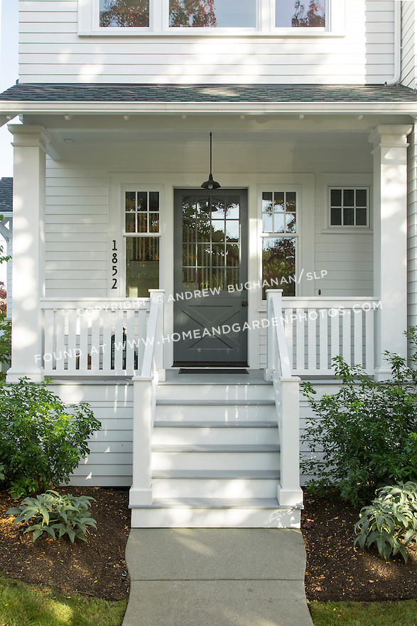 A small covered front porch welcomes visitors to this traditional home. This image is available through an alternate architectural stock image agency, Collinstock located here: http://www.collinstock.com