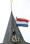 Foto: VidiPhoto<br /> <br /> DODEWAARD - Toch een uitbundig vlagvertoon voor prinses Beatrix maandag, mede dankzij de harde wind.  Zondag werd de oud-vorstin 78 jaar geworden. Omdat er die dag echter traditiegetrouw niet gevlagd wordt, gebeurde dat vandaag, zoals hier vanaf de toren van de hervormde kerk in Dodewaard. De prinses kondigde haar terugtreden aan op 28 januari 2013, drie dagen voor haar 75e verjaardag. Het vrijwillig pensioen betekende niet dat de prinses volledig uit beeld verdween. Zo was ze bij de nationale herdenking voor de slachtoffers van de neergeschoten vlucht MH17, maar ook bij de vieringen van 200 jaar Koninkrijk.