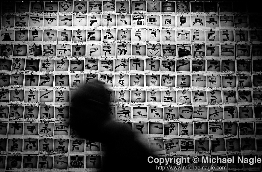 NEW YORK  --  SEPTEMBER 17, 2003:  An undercover officer in the NYPD Firearms Investigation Unit walks by a wall tiled with polaroids taken of guns bought in 2002 in their Manhattan office on September 17, 2003 in New York City.  The Unit bought over 486 guns off of the streets in 2002.  (PHOTOGRAPH BY MICHAEL NAGLE)