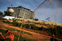 Ethnic Cham Muslim children play volleyball in front of a hotel under construction on banks of Mekong river in Phnom Penh July 30, 2013. About 100 ethnic Cham families, made up of nomads and fishermen without houses or land who arrived at the Cambodian capital in search of better lives, live on their small boats on a peninsula where the Mekong and Tonle Sap rivers meet, just opposite the city's centre. The community has been forced to move several times from their locations in Phnom Penh as the land becomes more valuable. They fear that their current home, just behind a new luxurious hotel under construction at the Chroy Changva district is only temporary and that they would have to move again soon.   REUTERS/Damir Sagolj (CAMBODIA)