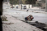 A Syrian civilian falls down on the street with a shot at his stomach as he tries to scape from the line of fire after he was already targeted at his back by one Syrian army sniper while was walking at the front line in Bustan Al-Bashar, northeast of Aleppo City.