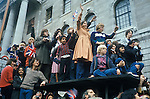 Silver Jubilee  London UK. Crowds rather and climb onto a bus shelter roof to get a better view of the Royal procession. 1977