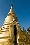 A gilded chedi (or stupa) rises in the Temple of the Emerald Buddha (Wat Phra Kaew), a shining complex of buildings within the grounds of the Grand Palace in Bangkok, Thailand. The Grand Palace (or Phra Borom Maha Ratcha Wang, in Thai) was built on the east bank of the Chao Phraya River starting in 1782, during the reign of Rama I. It served as the official residence of the king of Thailand from the 1700s to mid 1900s.