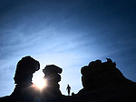 man and sunshine surrounned by silhouetted sandstone rock formation pinnacles.  mesa de cuba, northern new mexico, usa.