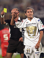 Chilean referee Ruben Selman shows the yellow card to UNAM Pumas forward Jose Luis Lopez during their qualifiying game for the Copa Libertadores at the University Stadium, March 8, 2006. International won 2-1 to UNAM Pumas. Photo by Javier Rodriguez