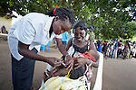 Estelle Agnes Astolo vaccinates a baby in Nimule, South Sudan, during a mobile clinic run by Caritas of the Diocese of Torit. The mobile clinic was launched in January 2014 shortly after war broke out within South Sudan, and thousands of families arrived in this area, near the country's border with Uganda, from Bor, in Jonglei State. Yet many have not been warmly welcomed to this region of Eastern Equatoria State, where two earlier waves of displaced people in the 1980s and 1990s left relations tense between the newcomers, who are Dinka, and the largely Ma'adi residents around the city of Nimule. The ACT Alliance is helping the displaced families and the host communities affected by their presence, and is supporting efforts to reconcile the two groups. The ACT Alliance also supports the Caritas mobile clinic, which provides medical care--often under a tree--both to displaced families as well as to poor residents of the host communities. Many of the newly arrived displaced families have not had their children vaccinated.