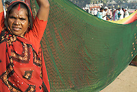 An Indian woman in a red sari with black detail holds a green sari out to dry, careful to keep it out of the dust, after the Janadesh Walk for Land, October 2007