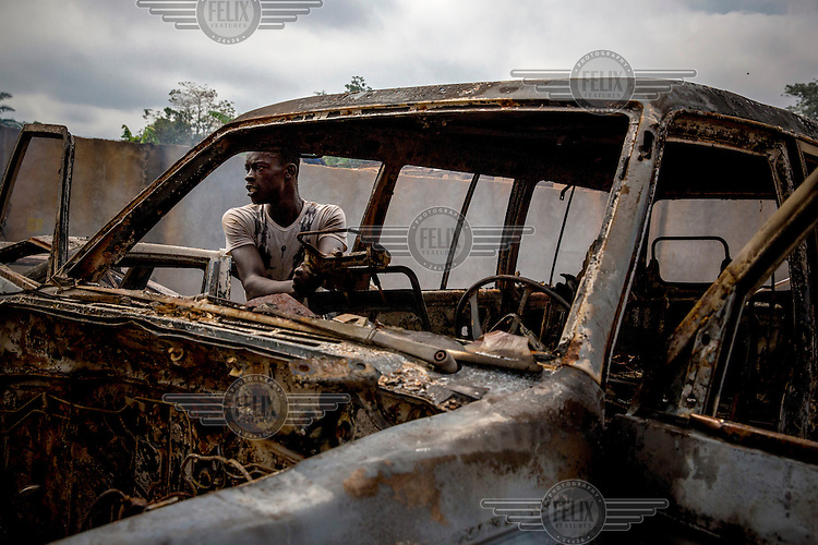 A looter tries to dismantle a burned out car. In 2013 a rebellion by a predominantly Muslim rebel group Seleka, led by Michel Djotodia, toppled the government of President Francios Bozize. Djotodia declared that Seleka would be disbanded but as law and order collapsed the ex-Seleka fighters roamed the country committing atrocities against the civilian population. In response a vigillante group, calling themselves Anti-Balaka (Anti-Machete), sought to defend their lives and property but they then began to take reprisals against the Muslim population and the conflict became increasingly sectarian. French and Chadian peacekeeping forces have struggled to contain the situation and the smaller Muslim population began to flee the country.
