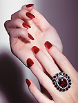 Closeup of woman hands with shiny red nail polish and a red stone ring