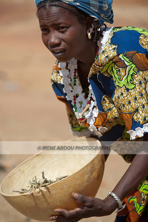 A Fulani woman in the town of Djibo in northern Burkina Faso uses wind power to separate milet grain from chaff.