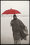 Woman with red umbrella in wind and rain on beach in Maine.