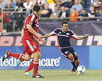 New England Revolution midfielder Diego Fagundez (14) dribbles. In a Major League Soccer (MLS) match, the New England Revolution (blue) defeated Chicago Fire (red), 2-0, at Gillette Stadium on August 17, 2013.