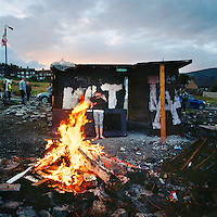 Youths in the loyalist Upper Ardoyne part of Belfast prepare for the bonfire to be set alight on the evening of 11 July. This event - the '11th Night' - marks the official start to the July celebrations. It is followed by 'The Twelfth' (also known as Orangemen's Day) which celebrates the 'Glorious Revolution' of 1688 (when Protestant king William III ascended the English throne) and the Battle of the Boyne (when William III defeated the catholic claimant James on the east coast of Ireland). Young people in Protestant estates such as this spend weeks scavenging for wood and other materials used to build the structure and even stand watch in the evenings leading up to July 11th as they fear that the it may be attacked and destroyed by rival Catholic youths.