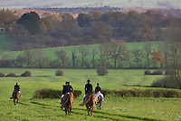 Members of Heythrop Hunt in fields on rolling hillside at Westcote, The Cotswolds, Oxfordshire, UK