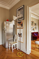 A shiny stainless steel fridge is situated in one corner of the kitchen where through the open door the living room can be glimpsed