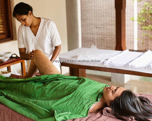 Young woman receiving an Aloe and Honey Herb body wrap, part of the 135-minute  Sahana Coconut Skin Treat spa treatment at Sahana Spa, Saman Villas, Aturuwella, Bentota, Sri Lanka.