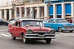 Havana, Cuba; a classic red 1950's Plymouth serves as a taxi along the Paseo de Marti