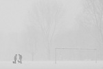 Two figures play with their dogs on a snow covered soccer (football) field in the Erasmuspark in Amsterdam, the Netherlands.