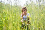 Allison McLamb, 8, of Hillsborough, NC, eats strawberries as she hides in a field covered with Crimson Clover and Winter Rye while visiting a U-Pick strawberry patch with her family at the Whitted Bowers certified Organic and Biodynamic farm in Cedar Grove Tuesday, May 5, 2015.