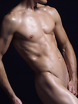 Young nude man with fit lean muscular naked body isolated on black background