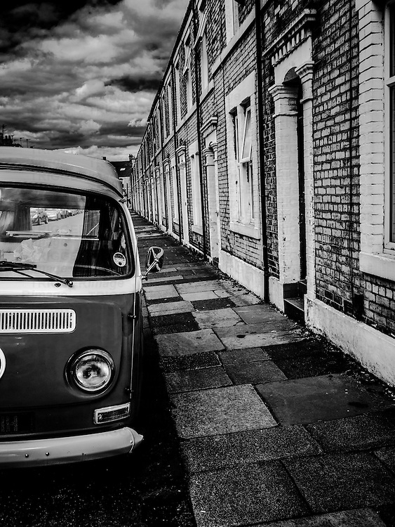 VW campervan on the street beside terraced houses