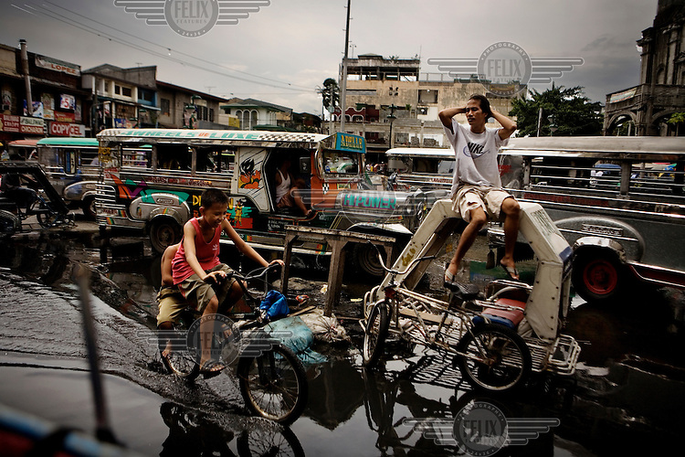 Floods in the busy streets of Manila. The driver of the rickshaw (sitting on it's roof) is named Dante Varona, 25 years old.