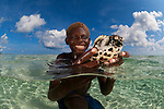Papuan boy holds his pet baby hawksbill turtle (Eretmochelys imbricata) split level in the shallows.